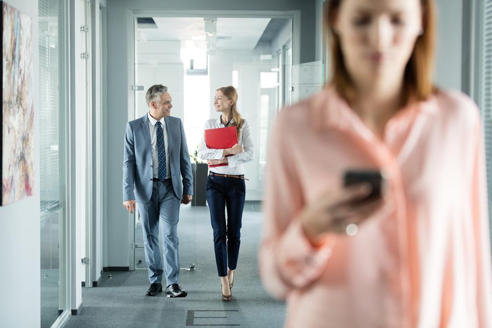 にこやかにオフィス内の廊下を歩く年配の男性と若い女性