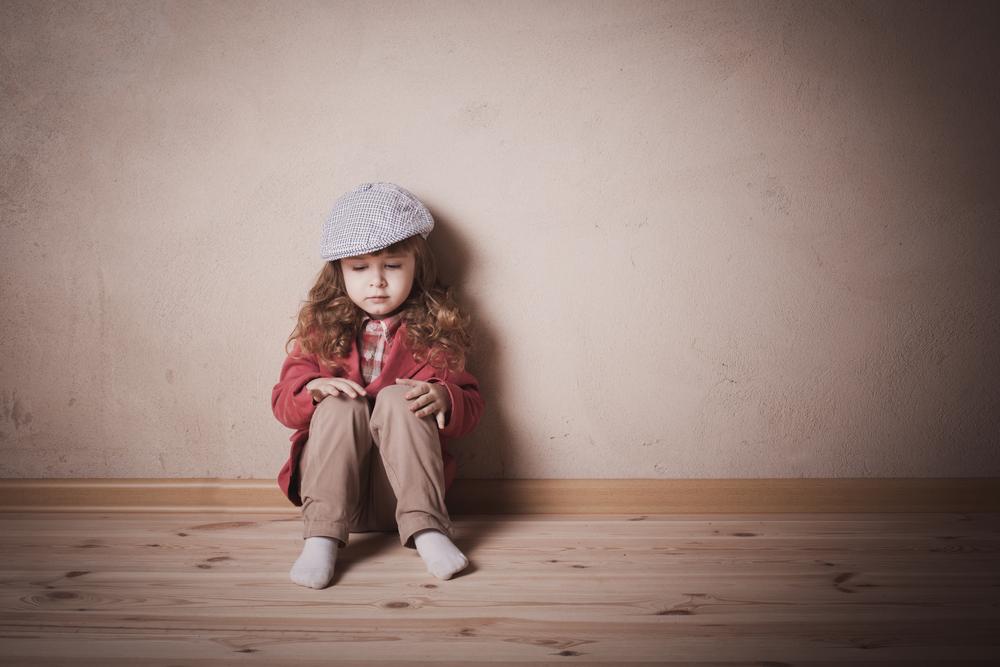ガランとした部屋の片隅に座り込む、さみしそうな少女